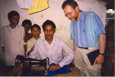 Peter Derrick with students learning how to sew